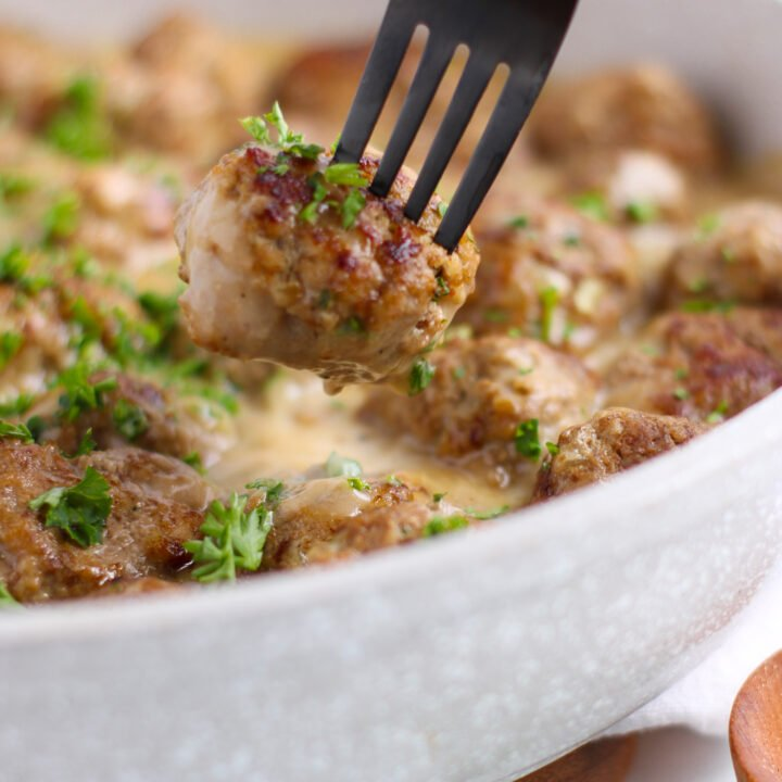 gluten free swedish meatball being picked up with a black fork ready to be enjoyed.