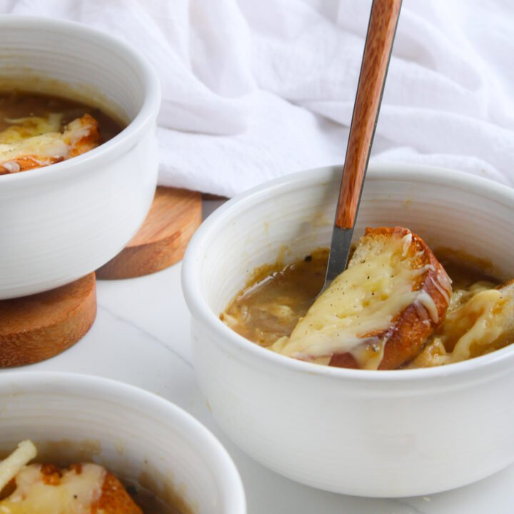 Gluten free french onion soup sitting in mini crock bowls topped with gluten free crusty bread and melted gruyere cheese