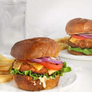 gluten free crispy chicken sandwiches topped with cheese, lettuce, tomatoes, onions and mayo ready to be eaten.