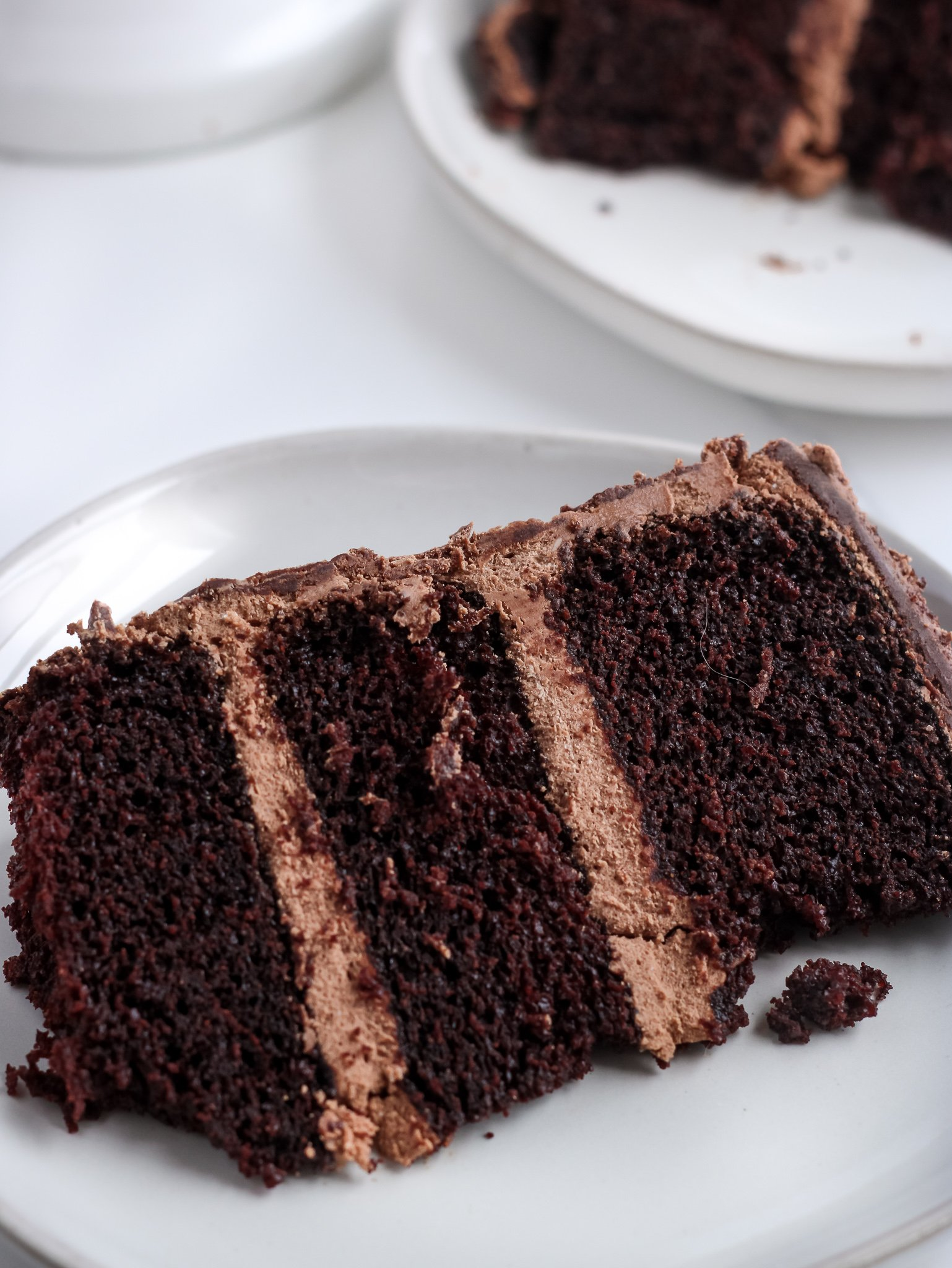 A slice of gluten-free chocolate cake with chocolate swiss meringue buttercream sitting on a alight grey plate.
