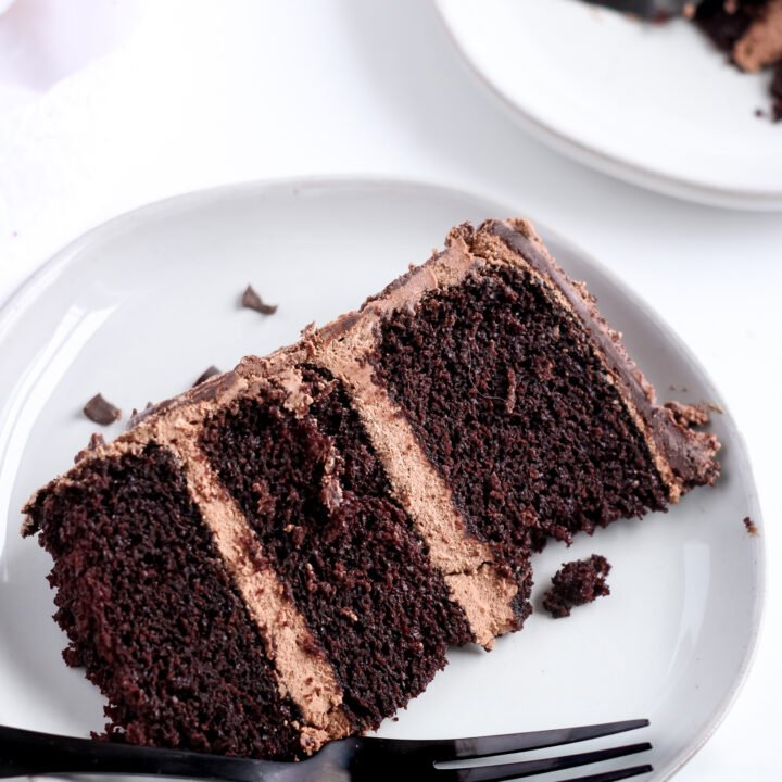 A prefect slice of gluten-free chocolate cake with grain-free swiss meringue buttercream frosting sitting on a grey plate ready to be eaten with a black fork.
