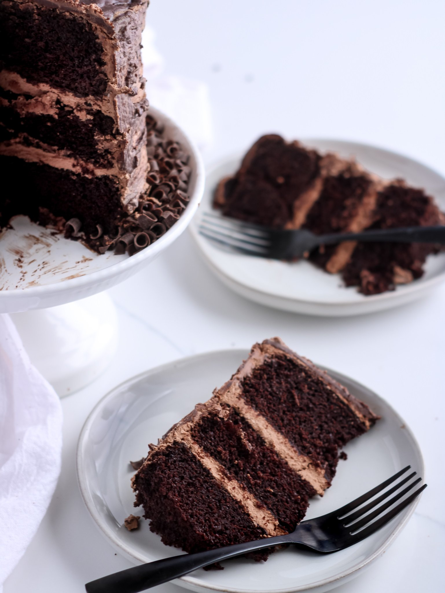 Gluten-free chocolate cake being slice from a white cake stand and being served onto light grey plates with black forks.