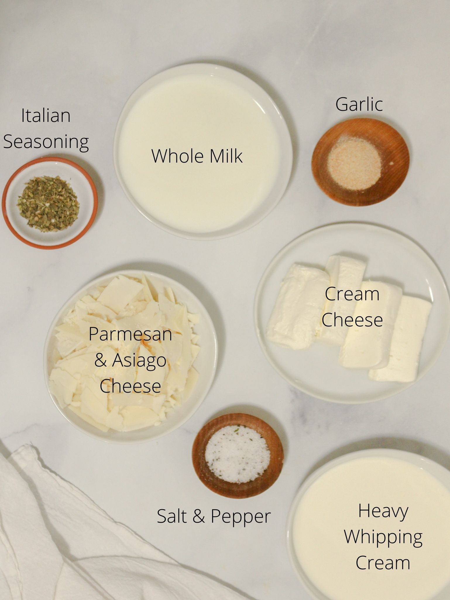 Homemade alfredo sauce ingredients laid out including milk, heavy cream, cream cheese, parmesan and asiago cheese, italian seasoning, garlic and salt and pepper.