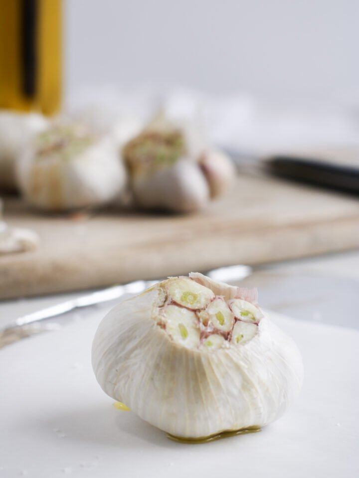 A head of garlic is sitting on parchment paper over a piece of aluminum with it's top cut off, drizzled with olive oil and a sprinkle of sea salt. All that's left to do is wrap it up and roast it.