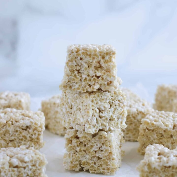 gluten free rice krispie treats in a stack sitting on a marble counter.