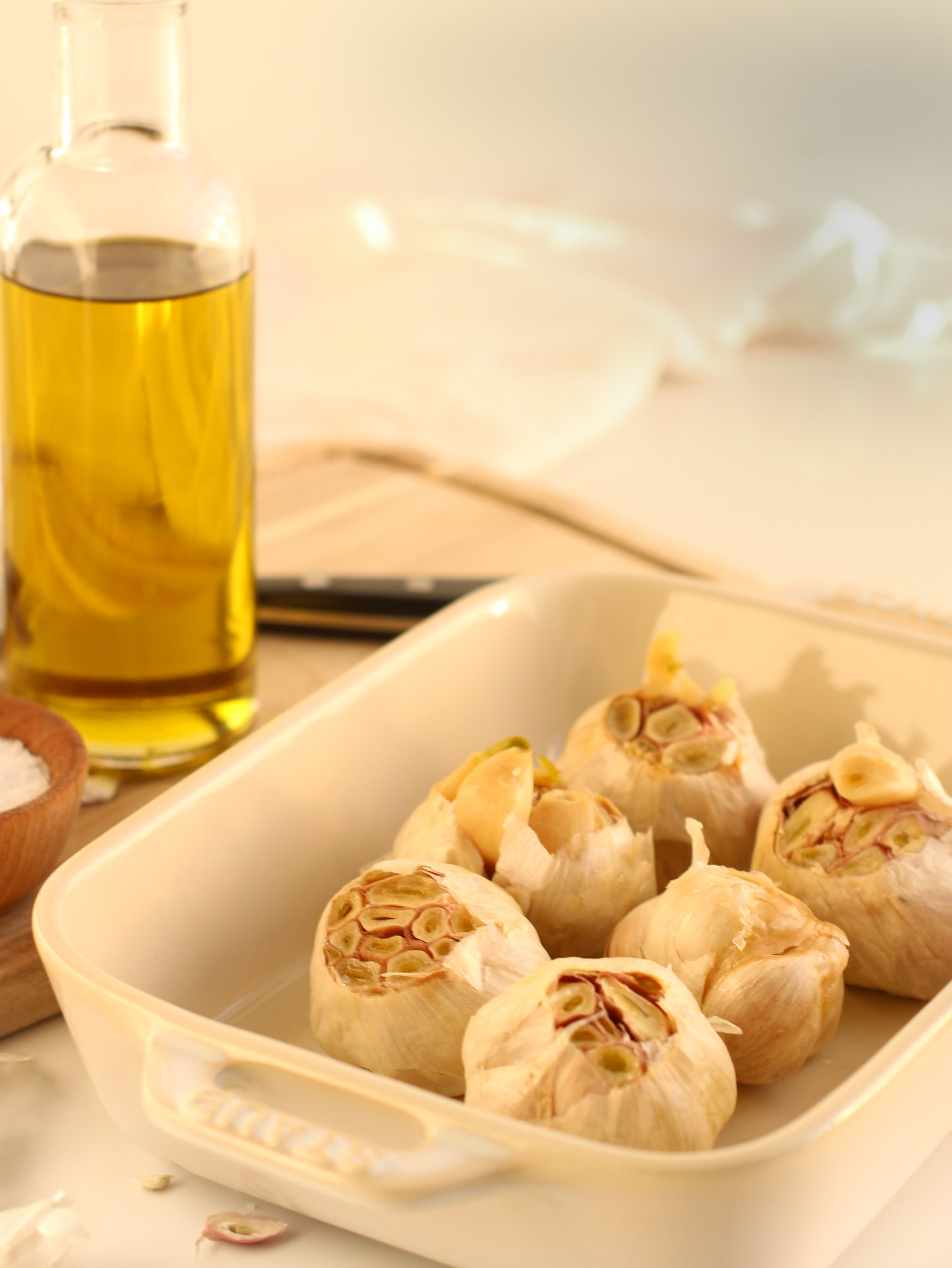 Cooked roasted garlic sitting in a white baking dish surrounded by garlic pieces, a bottle of olive oil and a small ramekin of salt ready to be used or stored for later.