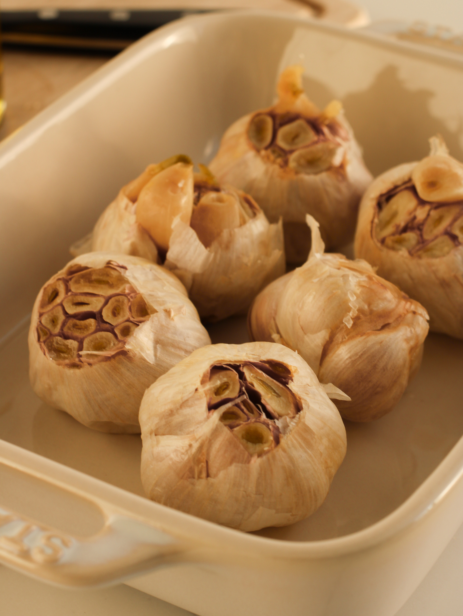 roasted garlic in a white baking dish partially squeezed out ready to be used or stored for later.