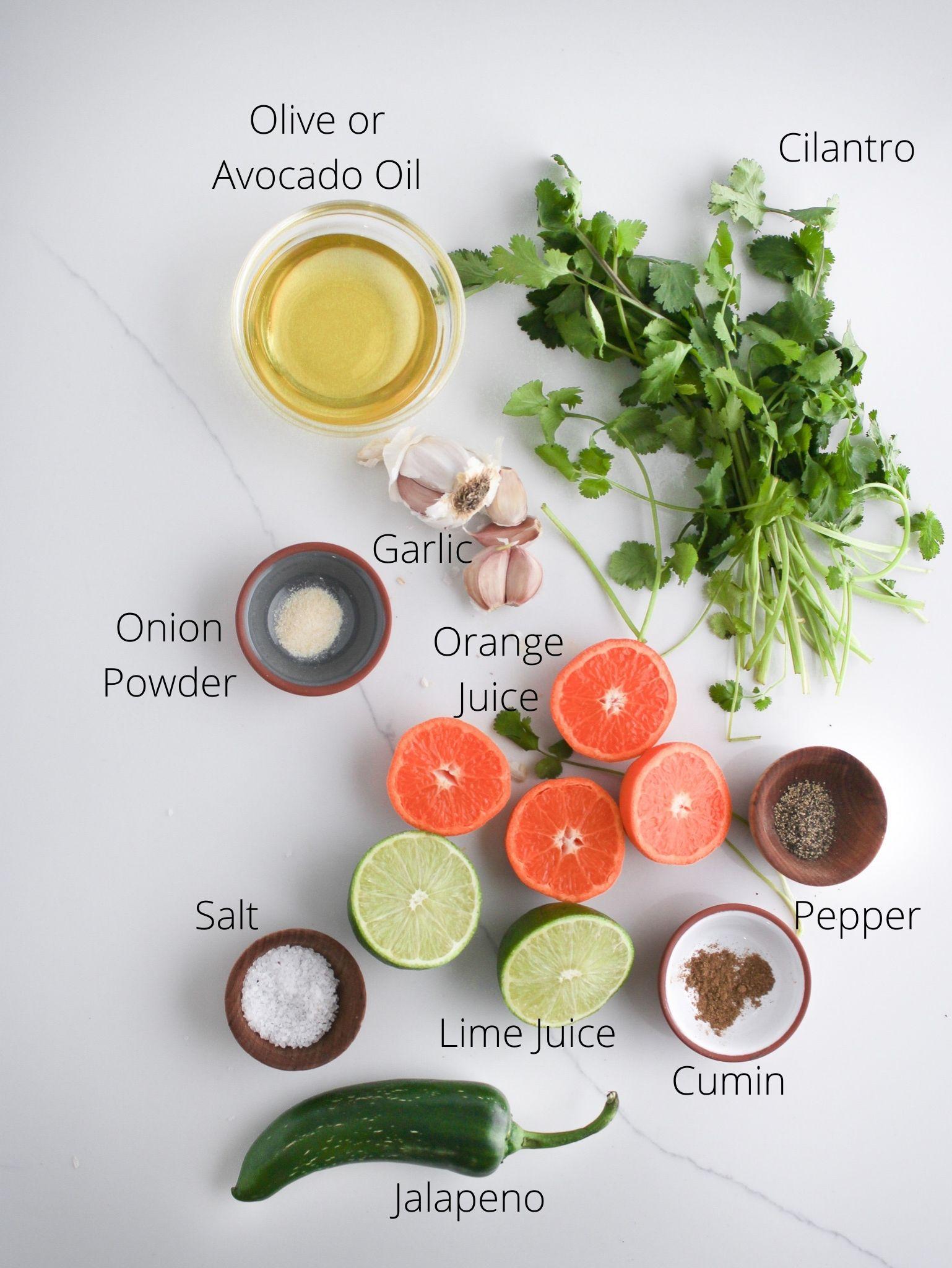 Carne asada ingredients laid out including olive or avocado oil, cilantro, garlic, lime juice, orange juice, jalapeno, onion powder, cumin, salt and pepper