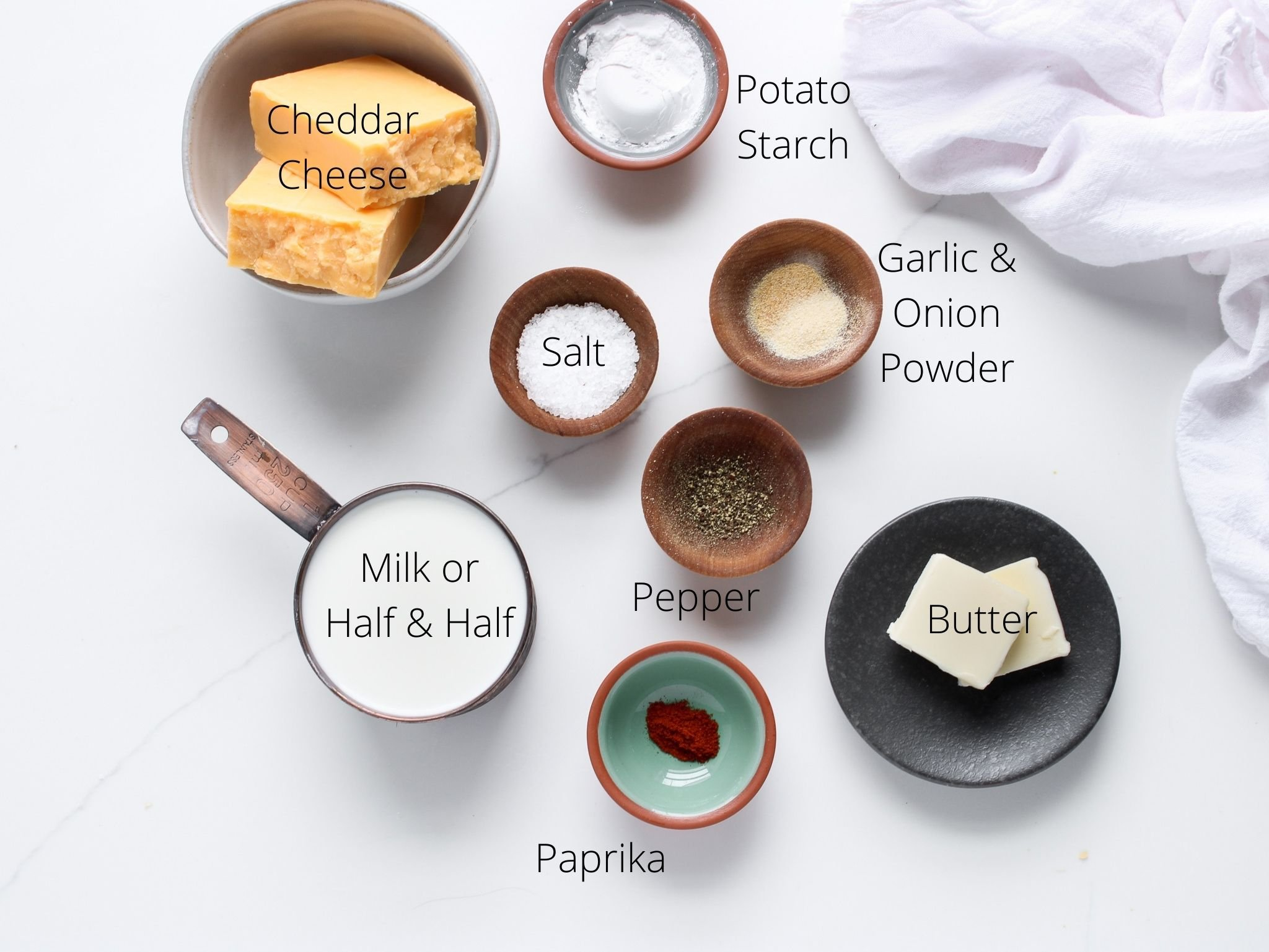 Gluten-free cheddar cheese sauce ingredients laid out including butter, potato starch, milk (of half and half), garlic, onion, paprika, salt, pepper and of course cheddar cheese ready to be turned into a creamy sauce.