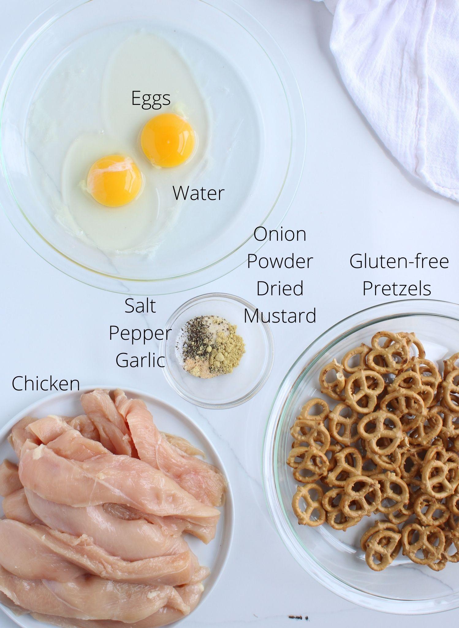 Gluten free pretzel crusted chicken ingredients laid out including chicken, gluten free pretzels, eggs, water, onion powder, salt, pepper, garlic and dried mustard.