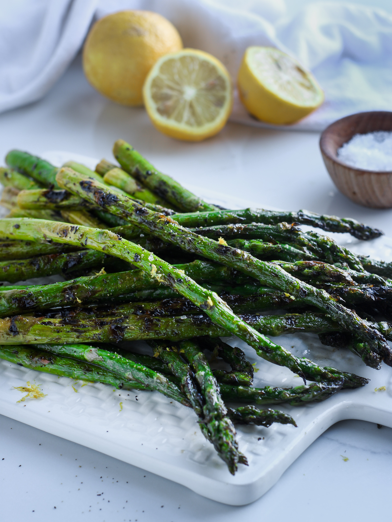 Grilled lemon and herb asparagus sitting on a white platter with sliced lemons and a small wooden bowl of salt in the background.
