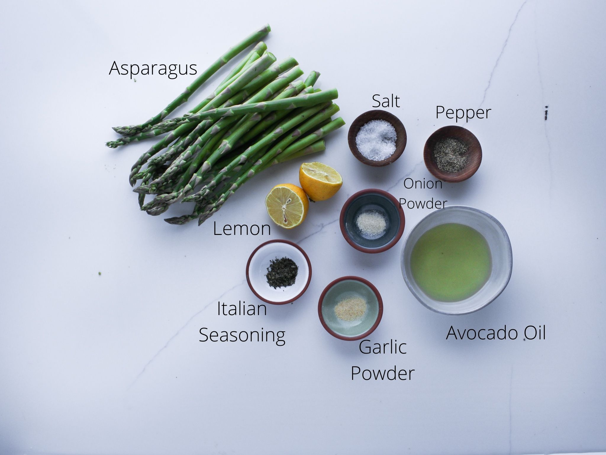 Grilled lemon and herb asparagus ingredients including asparagus, lemon, avocado oil, onion powder, garlic powder, italian seasoning, salt and pepper.