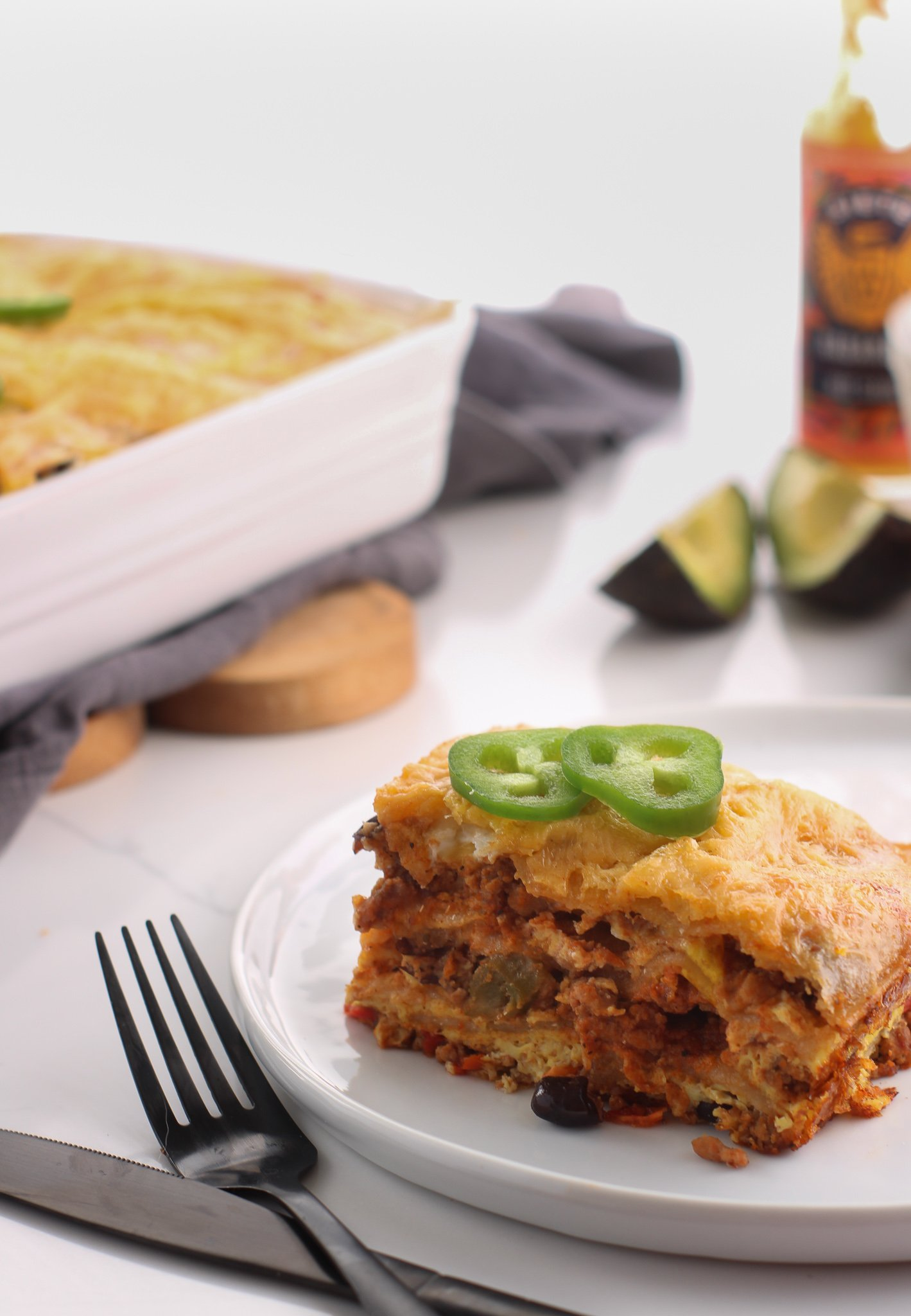 Slice of mexican breakfast casserole pulled out of the dish and onto a white plate with a few fresh jalapeno slices on top. There is some sliced avocado and hot sauce off to the side to add if wanted.