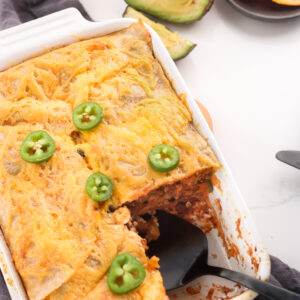 Gluten-free mexican breakfast casserole in a white baking dish with a slice taken out of the lower right hand corner and a serving spoon sticking in. The casserole is topped with a few sliced of fresh jalapeno with avocado on the side.