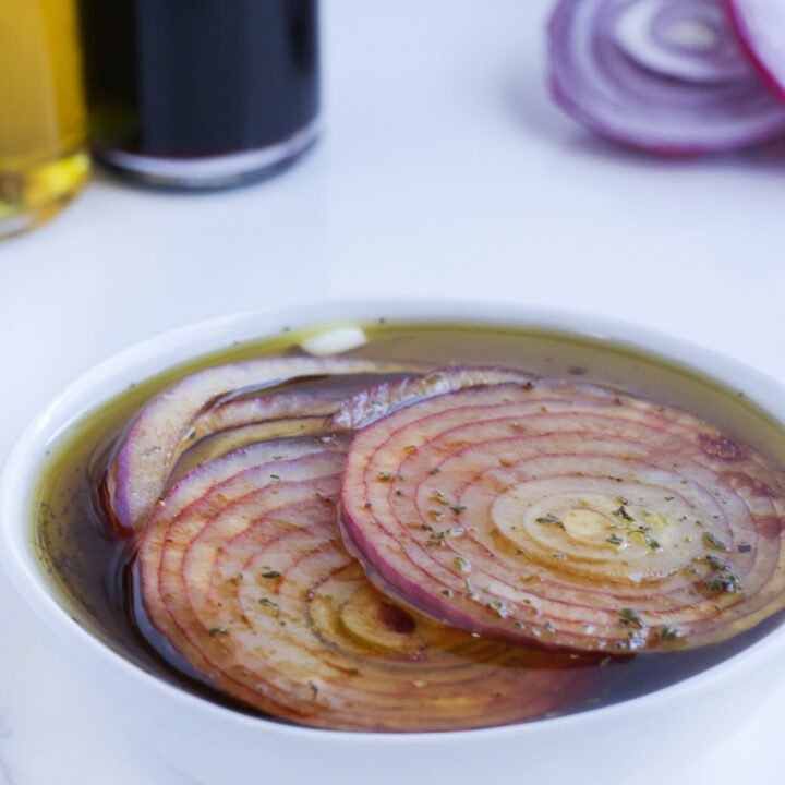 Marinated red onions covered and sitting in a white bowl with a bottle of balsamic vinegar and olive oil off to the left side and some more sliced onions off to the right.