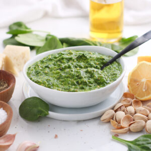 Pistachio spinach pesto sauce sitting in a white bowl with a black spoon surrounded by it's ingredients ready to be used in everything from pasta to chicken and even over veggies.