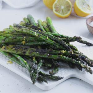 grilled lemon herb asparagus sitting on a white platter with fresh lemons over a white table linen.