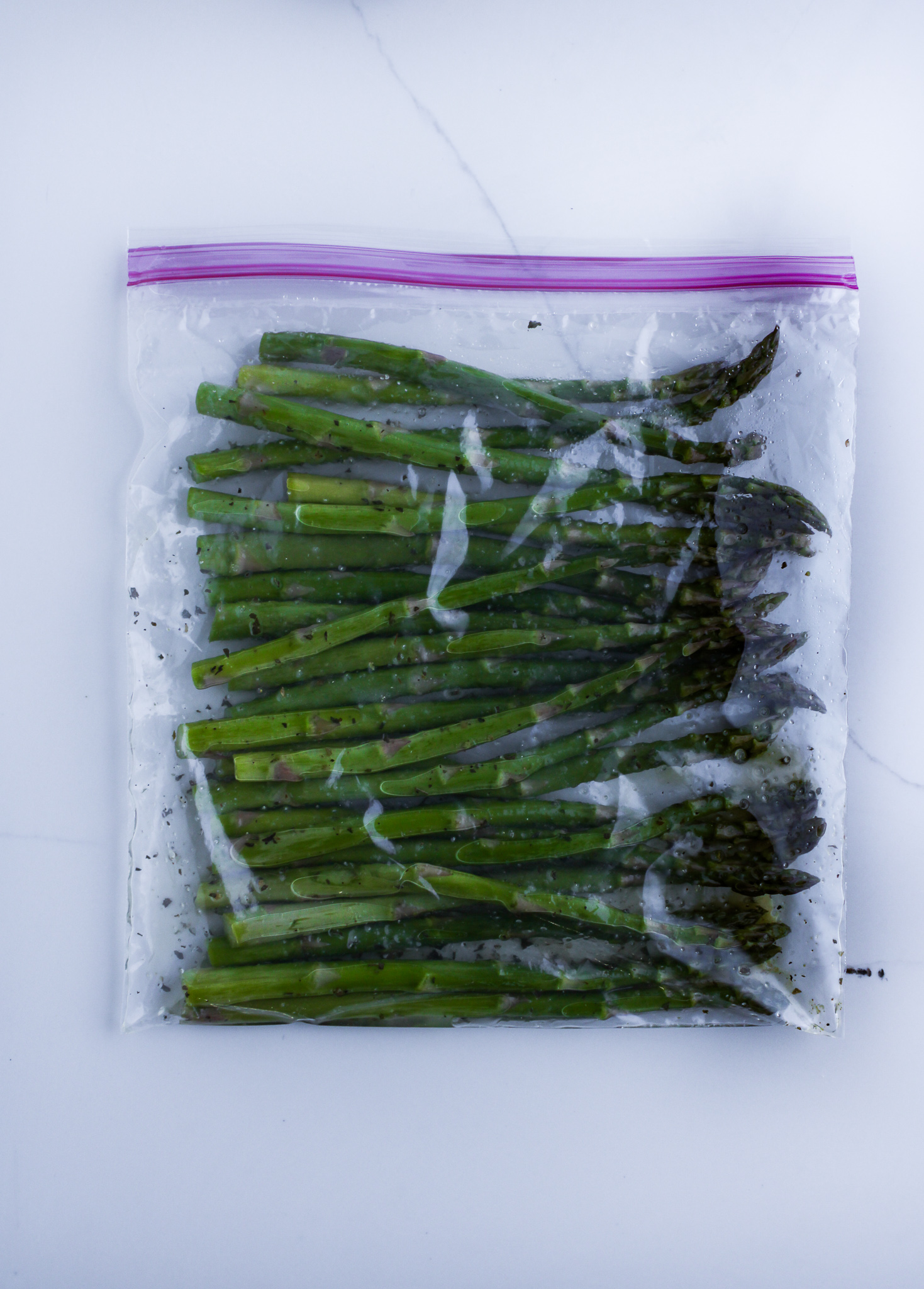 Asparagus marinating in the spices in a ziploc bag.