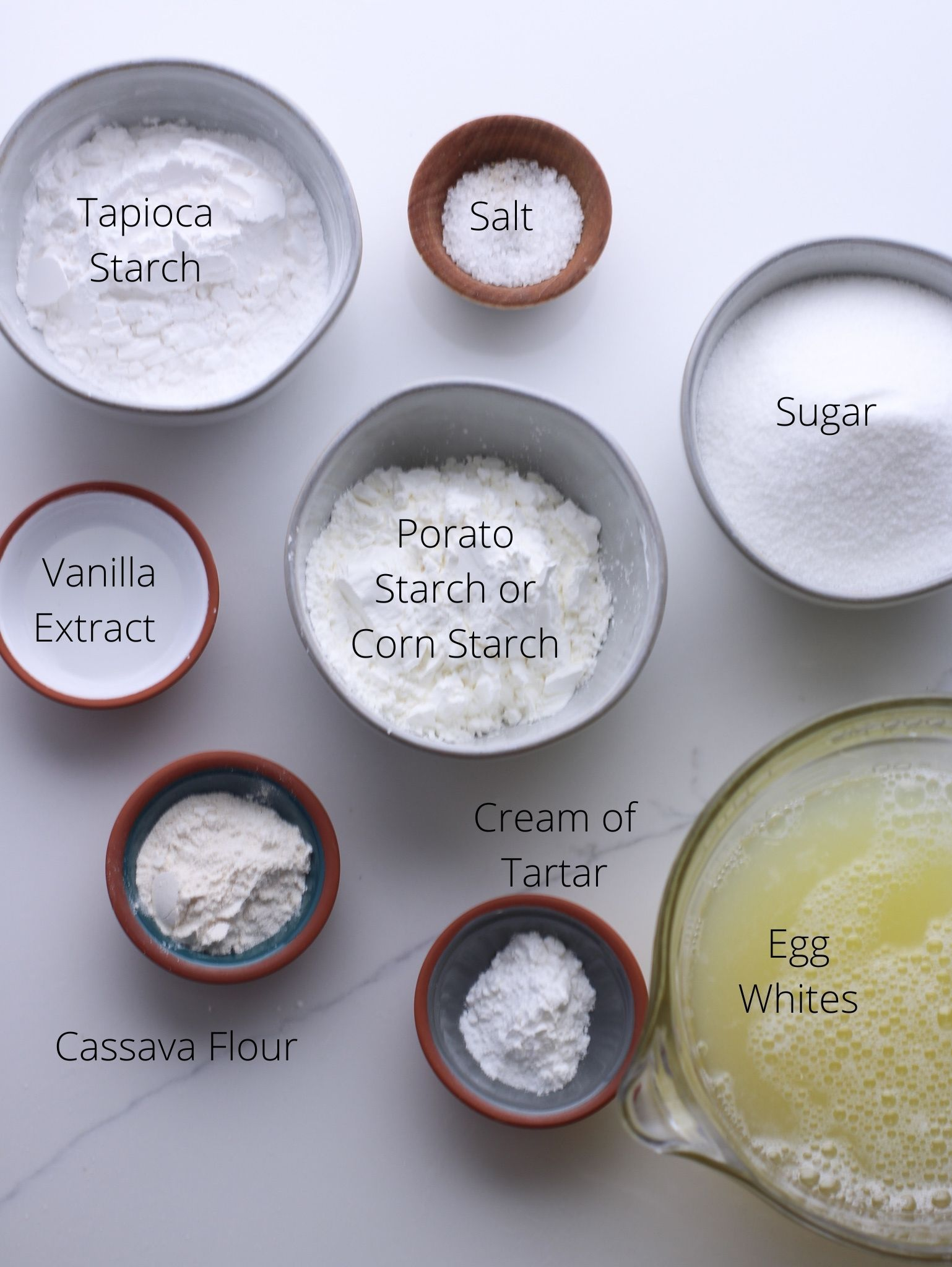 Ingredients laid out for gluten-free angel food cake including egg whites, sugar, cream of tartar, tapioca starch, potato or corn starch, cassava flour, salt and vanilla extract.