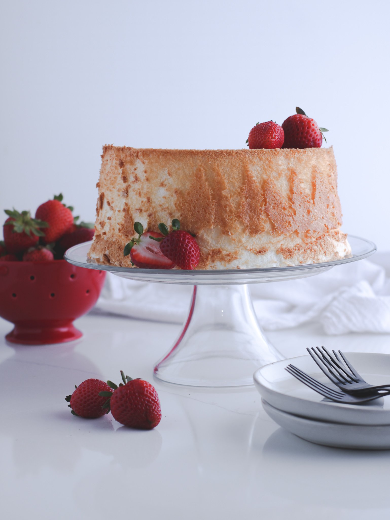 Angel food cake sitting on a glass cake stand surround by fresh strawberries and plates and forks to enjoy it once it's sliced.