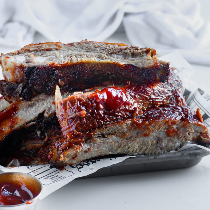 Gluten-free BBQ pork ribs cooked in the oven, finished on the grill and fall off the bone tender sitting on a lined metal pan with extra bbq sauce for dipping.