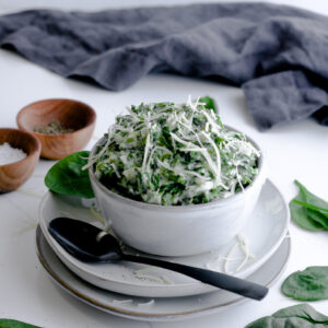 Creamed spinach sitting in a light gray bowl surrounded by more fresh spinach, salt and pepper with a black spoon ready to be enjoyed to the very last bite.