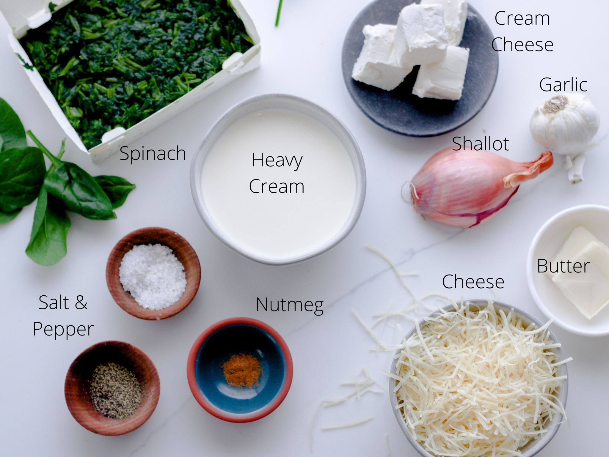 Creamed spinach ingredients including frozen spinach, heavy cream, cream cheese, shallow, garlic, butter, parmesan cheese, salt, pepper and nutmeg laid out and ready to be made into the easiest and cheesiest side dish.