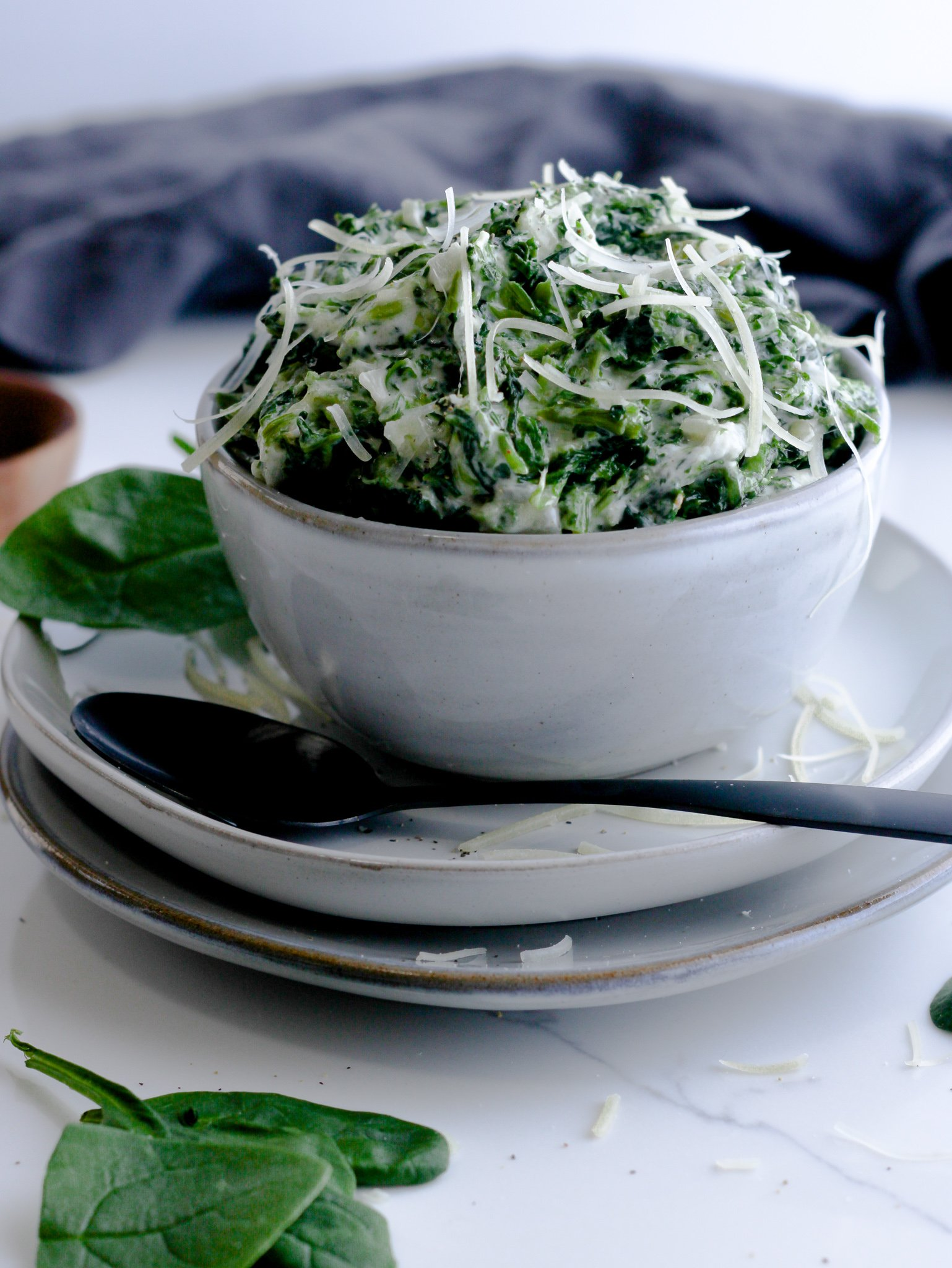 Creamed spinach made and sitting in a light gray bowl over two stacked gray plates surrounded by more fresh spinach and a gray table linen ready to enjoyed by the whole family.