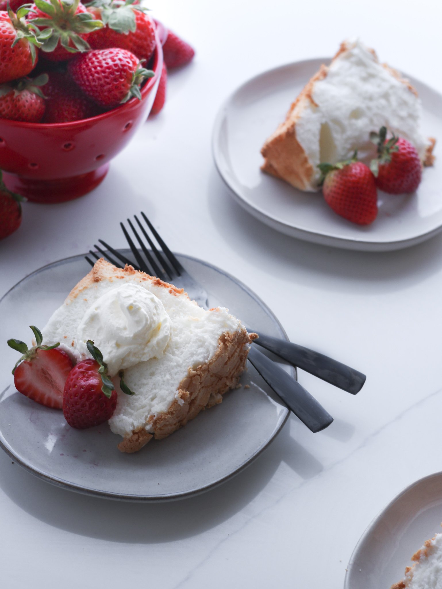Gluten-free Angel Food Cake sliced and being served on top of small light grey plates. There is a red bowl of fresh strawberries in the upper right hand corner. The center slice has a dollop of fresh whipped cream with some fresh sliced berries and black forks to be enjoyed with.