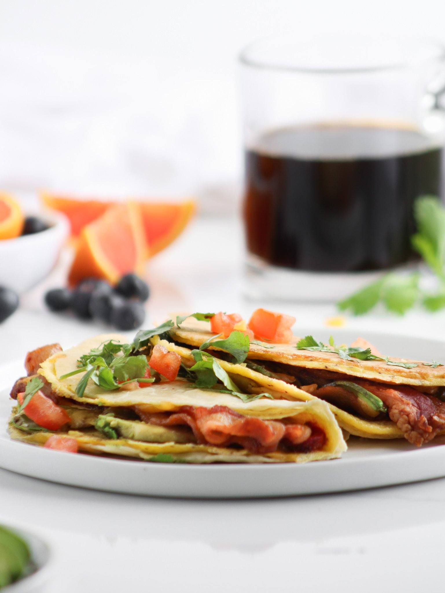 gluten-free crispy breakfast tacos sitting on a white plate topped with cilantro and fresh tomatoes with avocado, blood orange and blueberries with fresh coffee for an easy breakfast.