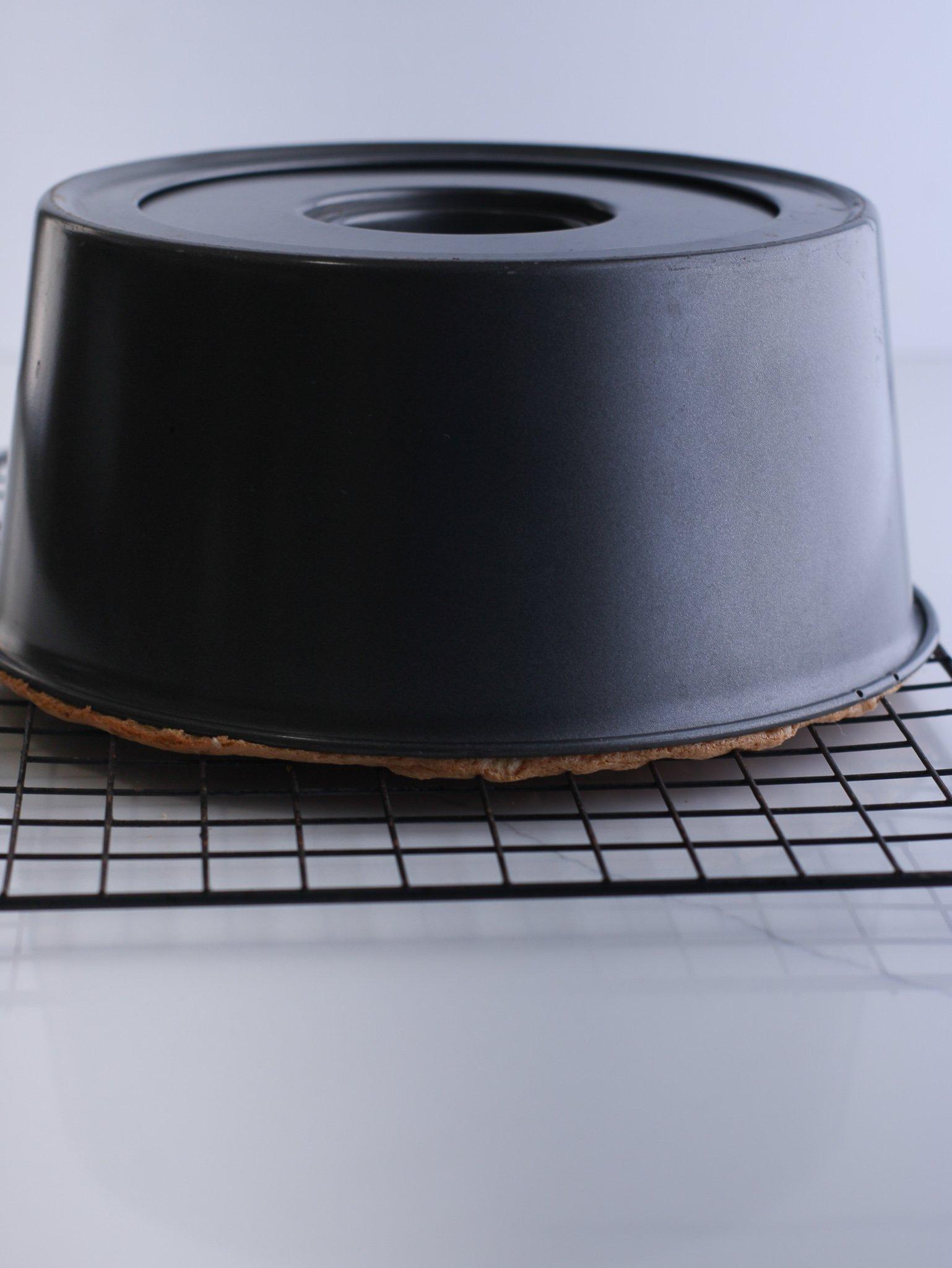 Angel food cake cooling upside down on a metal cooling rack.