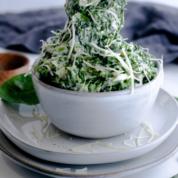 Creamed Spinach sitting in a light grey bowl on top of two light gray plates topped with more fresh parmesan. There is a spoon dug into it and pulling up to show off the creamy, cheesy texture.