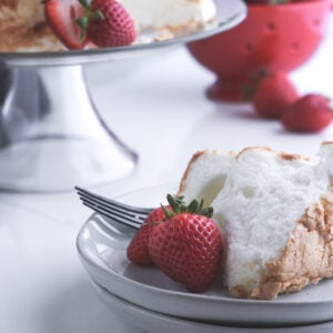 A slice of angel food cake sitting on top of light grey plates with a fresh berry. The rest of the cake is on the stand to the side along with a red bowl with more strawberries.