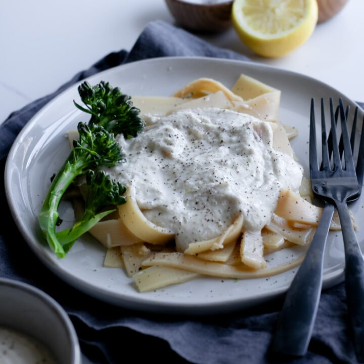 Gluten and dairy-free alfredo is topped over some hearts of palm alfredo noodles with some fresh broccolini ready to be eaten with some black forks and fresh lemon.