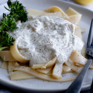 Gluten and dairy-free alfredo sauce sitting on a bed of hearts of palm pasta with some fresh steamed broccolini on a light gray plate with black forks over a dark gray table linen.