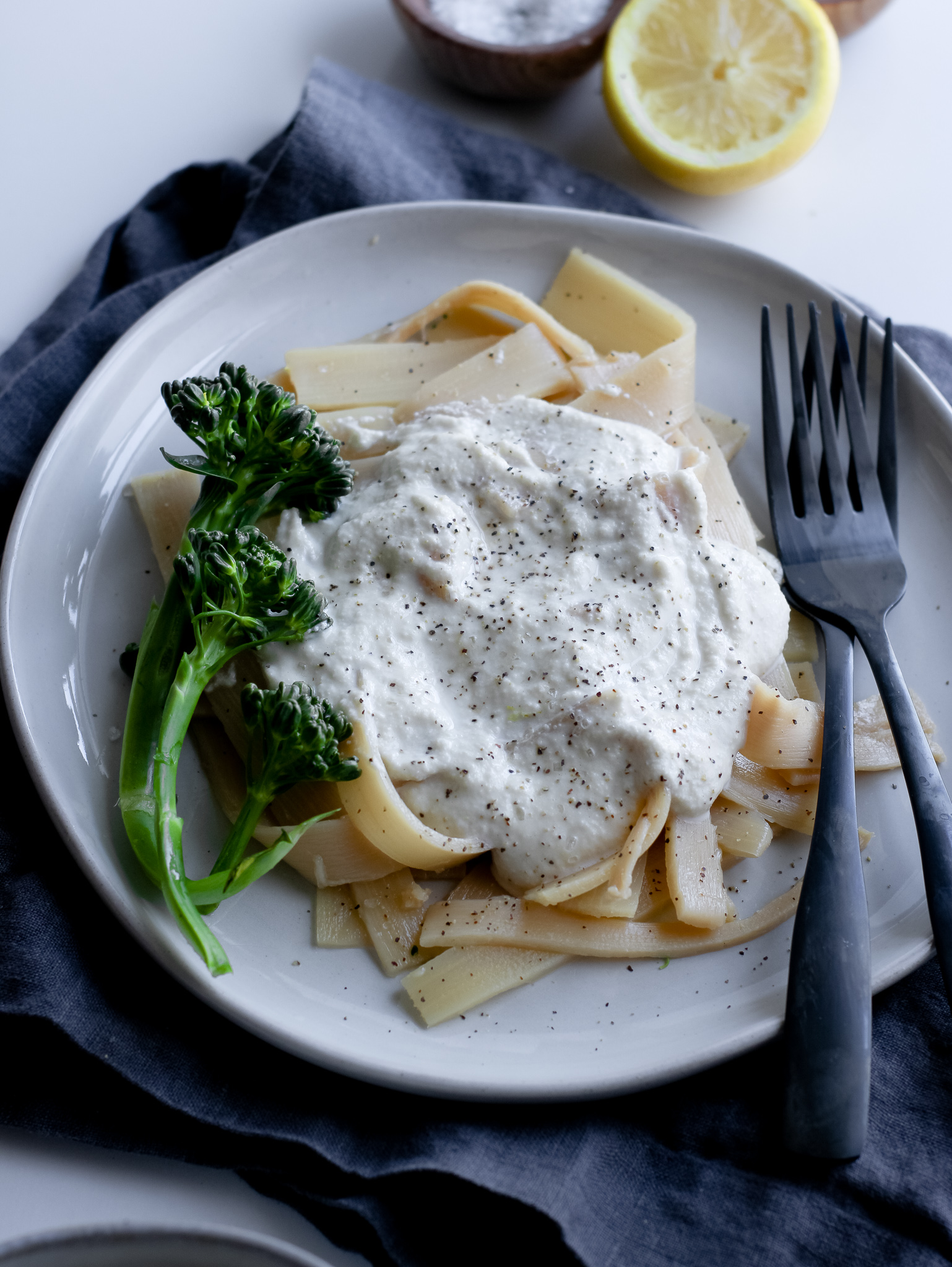 Gluten and dairy-free cashew alfredo sauce topped over some gluten-free pasta on a light gray plate and fresh steamed broccolini.