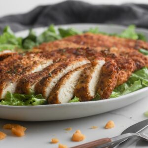 Sliced crispy cheddar chicken laying on a bed of greens.
